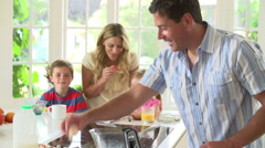 Father Making Scrambled Eggs For Family Breakfast In Kitchen Stock Footage