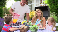Family Enjoying Outdoor Barbeque In Garden - stock footage