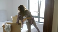 Stock Video Footage of Woman Moving Into New Home Unpacking Clothes In Bedroom