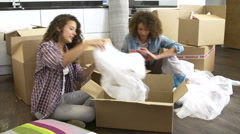 Two Women Moving Into New Home And Unpacking Boxes - stock footage