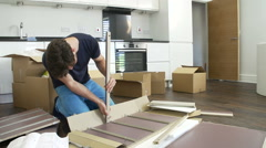 Man Putting Together Self Assembly Furniture In New Home Stock Footage