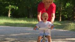 Grandmother assisting child to ride a bicycle in summer park Stock Footage