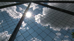 Dolly: Sun shining through the chain link iron wire fencing Stock Footage