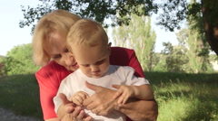 Grandmother and grandson holding hands smiling close-up - stock footage