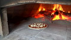 Cooking pizza into a wood over behind a big flame. Stock Footage
