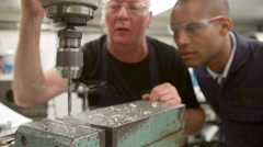 Engineer Showing Apprentice How To Operate Drilling Machine Stock Footage