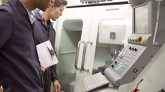 Two Engineers Monitoring Computerized Lathe - stock footage