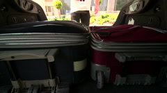 Man traveler taking out rollaboard luggage from the car trunk Stock Footage