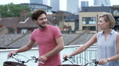 Couple Pushing Bikes With City Skyline In Background Stock Footage
