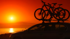 Car with mounted bicycles on summer beach at sunset - stock footage