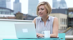 Young Woman Sitting On Roof Terrace Using Laptop Stock Footage