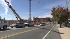 Cars driving past a construction site wide shot Stock Footage