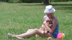 Child holding puppy dog on a grass - stock footage