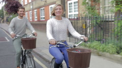 Stock Video Footage of Couple Cycling Along Urban Street Together