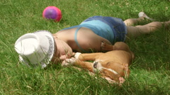 Child with puppy dreaming on grass in summer day - stock footage