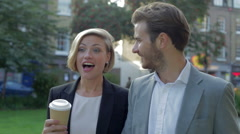 Business Couple Walking Through Park With Takeaway Coffee Stock Footage