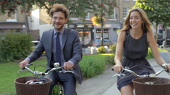 Businesswoman And Businessman Riding Bike Through City Park Stock Footage