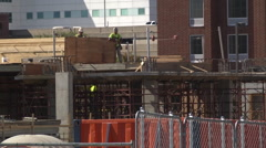 Construction workers building on scaffolding telephoto Stock Footage