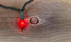 Stock Photo of red christmas light on rustic wood