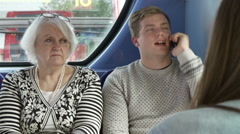 Woman Disturbed By Young Passengers On Bus Journey Stock Footage