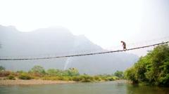Tourist woman crossing dangerous bamboo suspension bridge, laos Stock Footage
