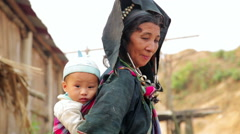 PONGSALI, LAOS - APRIL 2014: native Akha woman carry baby Stock Footage