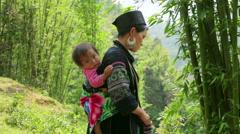 SAPA, VIETNAM - MAY 2014: tribal native Akha woman carry baby Stock Footage