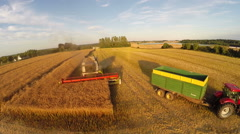 Tractor ready to pick up the Oilseed rape harvested by combine harvester - stock footage