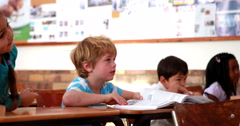 Cute pupils listening attentively in classroom - stock footage