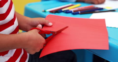 Cute little boy cutting paper shapes classroom Stock Footage