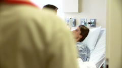 Female Doctor Talks To Husband And Wife In Hospital Room Stock Footage