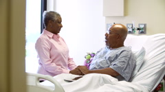 Female Doctor Talking To Senior Couple In Hospital Room Stock Footage