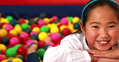 Cute girl smiling at camera in ball pool Stock Footage