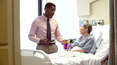 Consultant Talks To Senior Female Patient In Hospital Room Stock Footage