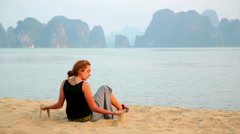 Tourist girl at beach, limestone view of halong bay, vietnam Stock Footage