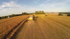 Following the cobine harvester down the Oilseed rape field Stock Footage