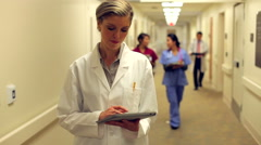 Doctor Walking Along Hospital Corridor Using Digital Tablet - stock footage
