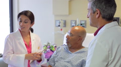 Medical Team Talking To Senior Male Patient In Hospital - stock footage