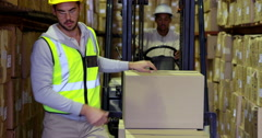 Warehouse worker packing boxes on forklift Stock Footage
