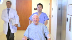 Senior Male Patient Being Pushed In Wheelchair By Nurse - stock footage