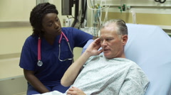 Nurse Examining Mature Male Patient In Hospital Bed Stock Footage
