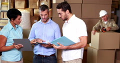 Warehouse operatives discussing file on tablet pc Stock Footage