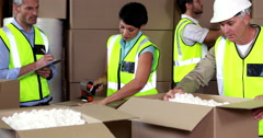 Team of warehouse operatives working together - stock footage