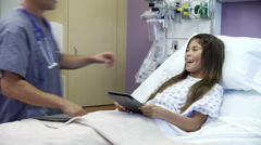 Young Girl Talking To Male Nurse In Hospital Room Stock Footage
