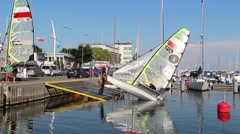 Man launching sailboat on the water 3 Stock Footage