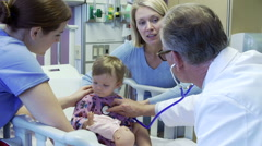 Mother And Daughter With Staff In Pediatric Ward Of Hospital Stock Footage