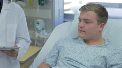 Male Patient Talking To Medical Staff In Emergency Room Stock Footage