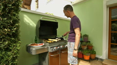 Man at gas barbecue Stock Footage