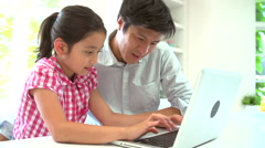 Asian Father Helping Daughter To Use Laptop At Home Stock Footage