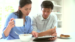 Asian Couple Looking At Digital Tablet Over Breakfast Stock Footage